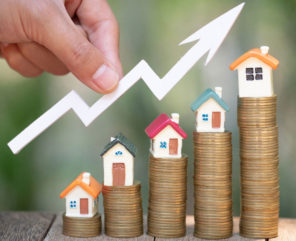 Coins with houses stacked in increase amounts to indicate property price growth.