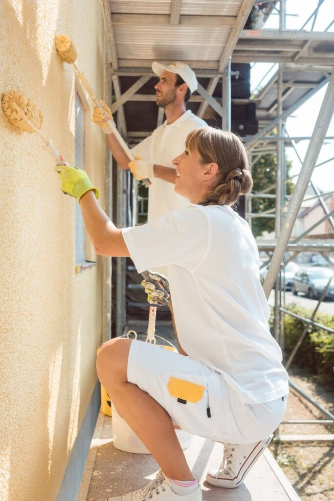 Two people painting the exterior of a building.  Buy to Let refurbishment - is it worth it?